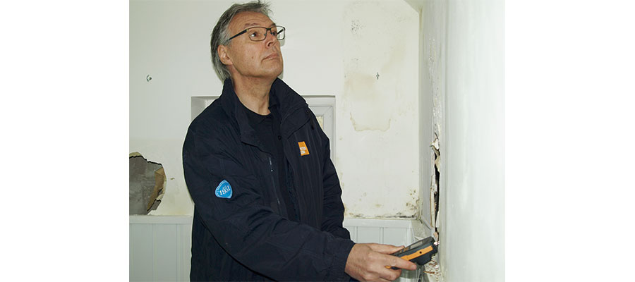 The Homes Act - A Peter Cox employee testing damp in a home
