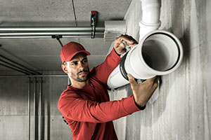 Plumber sorting out pipes and making sure fire safety measures are in place